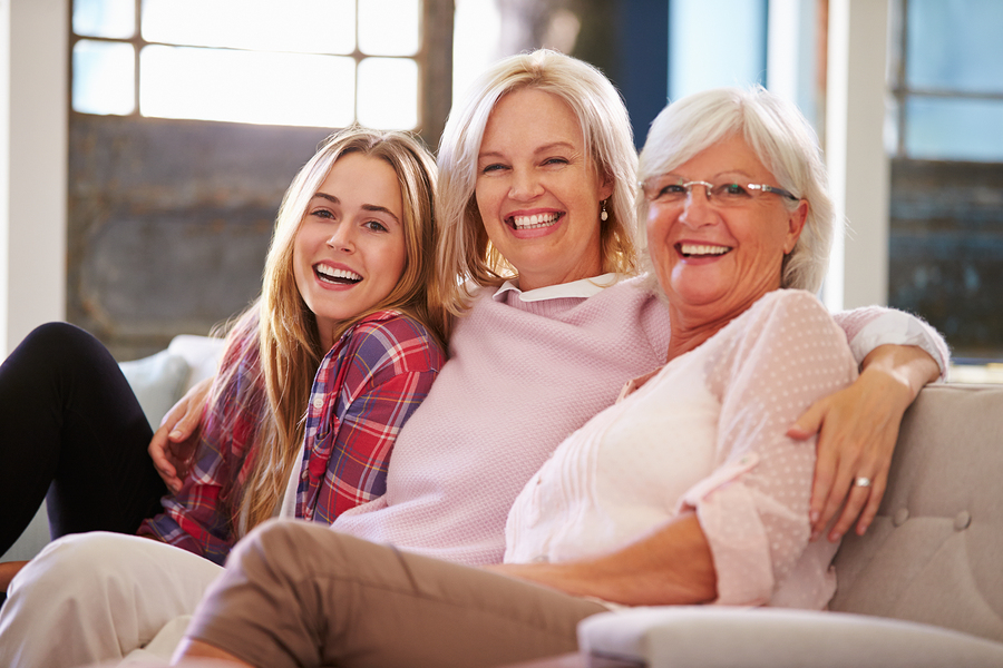 Grandmother With Mother And Adult Daughter Relaxing On Sofa